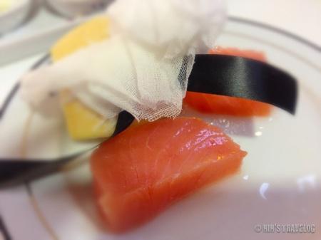 salmon mentah yang disajikan bersama irisan lemon, untuk mengurangi rasa amis