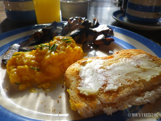 My breakfast consist of scrambled egg, sauteed mushroom and toasted home made bread.
