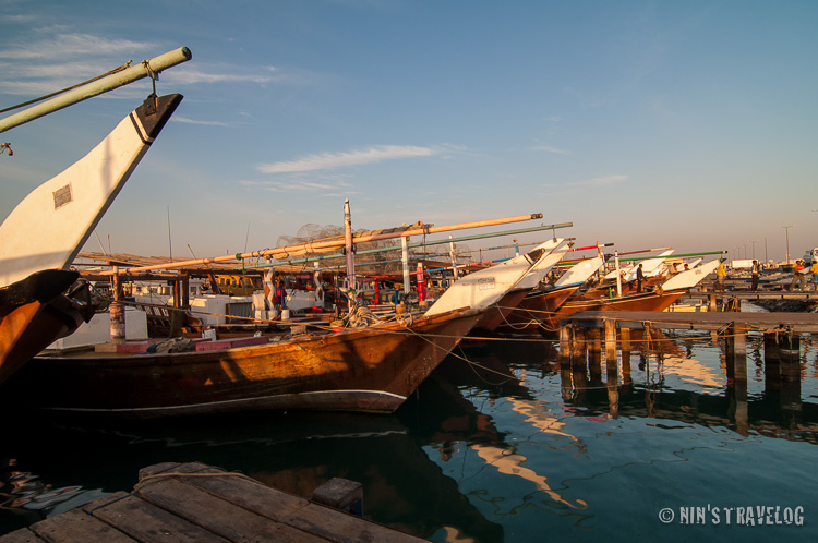 Approximately an hour after sunrise, the colour of the light still gives a warm shadow/reflection to the dhows