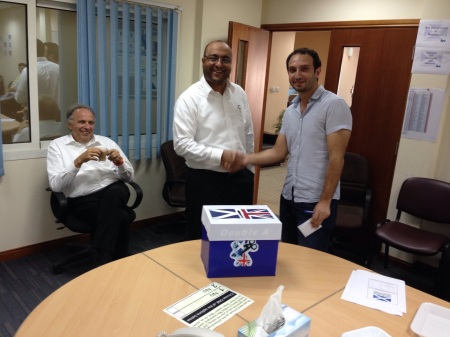 My Syrian, and Indian friends posing in front of the voting box, witnessed by my German colleague...