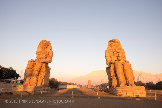 statues of Pharaoh Amenhotep III standing under the rays of the morning sun at Colossi of Memnon
